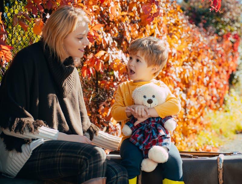 Piccolo figlio della mamma comunicare il fondo del fogliame di autunno Relazioni fiduciose Paternit? ed educazione Amore e fiduci immagini stock libere da diritti