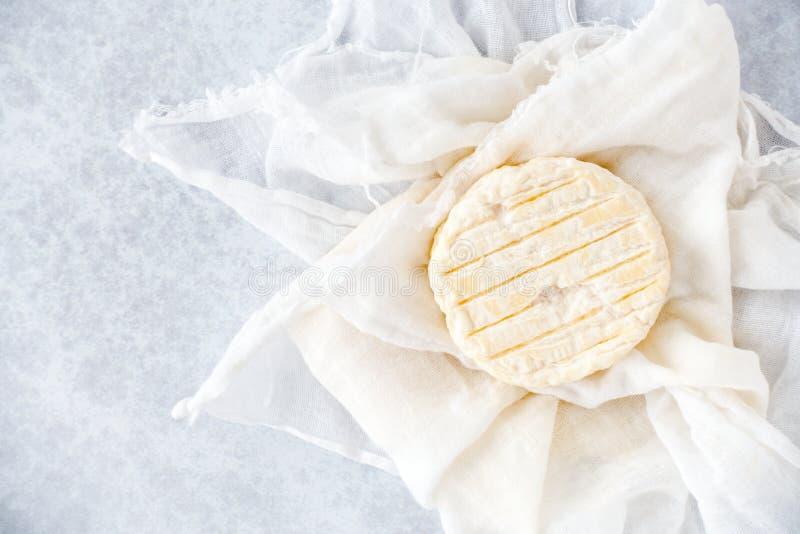 Piccolo formaggio a pasta molle rotondo della mucca sul panno della mussola e sul fondo blu fotografia stock libera da diritti