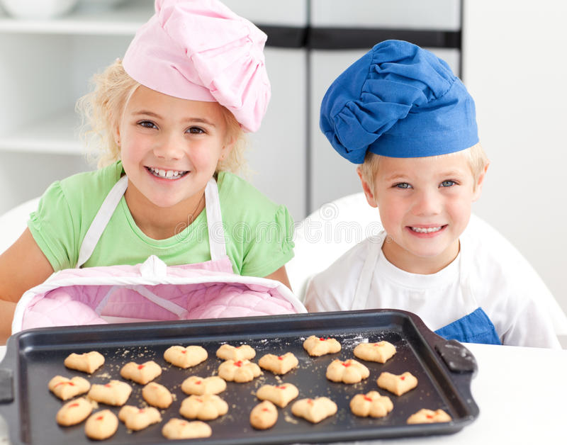Piccolo fratello e sorella felici con i biscotti immagini stock libere da diritti