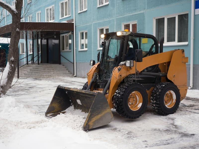Piccolo giallo pulendo le vie di un gran numero di neve in città dopo le precipitazioni nevose Uno spazzaneve che rimuove una str immagini stock