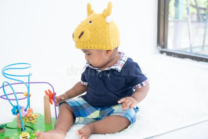 Piccolo giocattolo asiatico sveglio del gioco del neonato fotografia stock