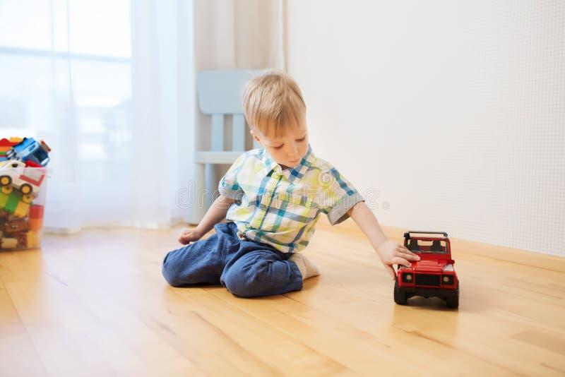 Piccolo giocattolo del neonato che gioca con l'automobile a casa immagini stock