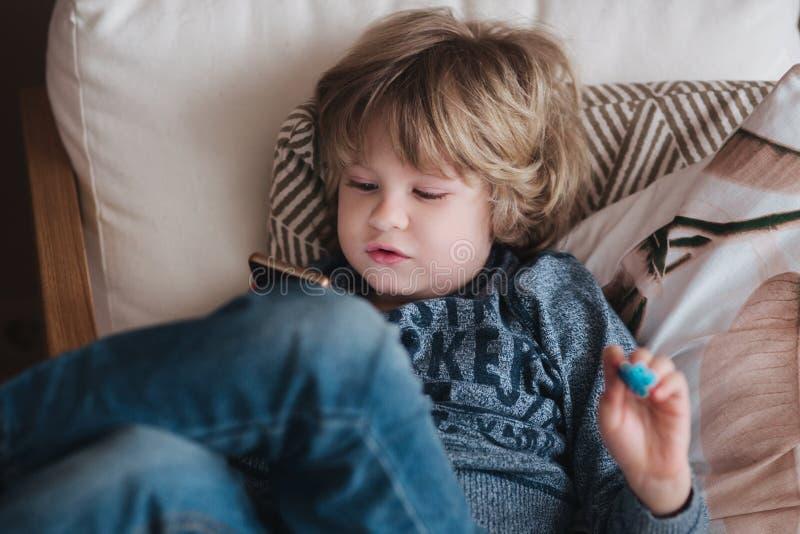 Piccolo gioco online sveglio del gioco del ragazzo al telefono cellulare a casa Concetto di dipendenza fotografie stock
