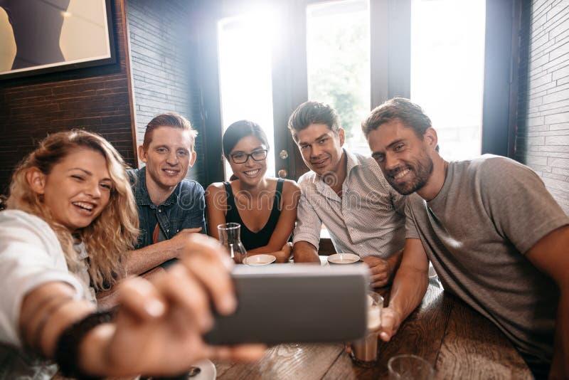 Piccolo gruppo di amici che prendono selfie su un telefono cellulare fotografia stock