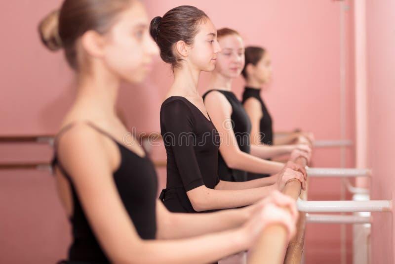 Piccolo gruppo di ballerine adolescenti che praticano in uno studio di balletto fotografie stock libere da diritti
