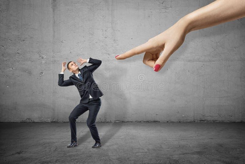 Piccolo imprenditore che pende a sinistra e che riguarda la sua testa di mani che provano a proteggersi dalla mano della donna en fotografia stock libera da diritti