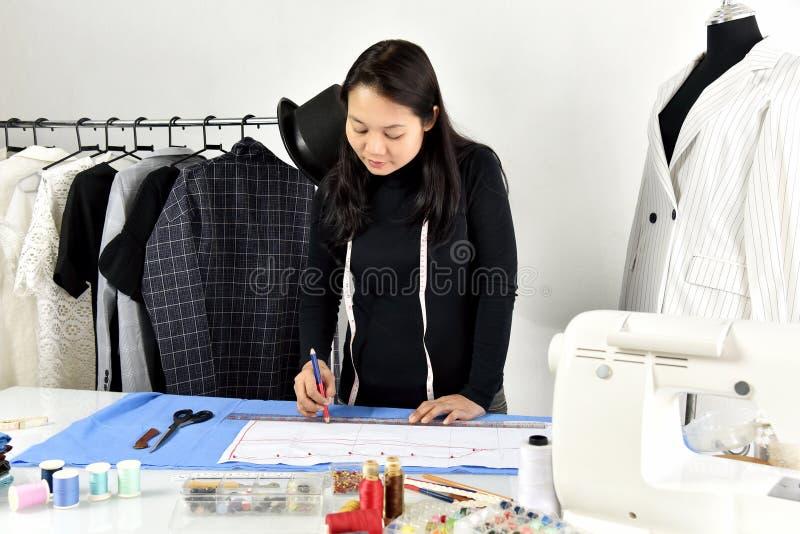 Piccolo imprenditore, progettista del sarto da donna che fa modello e l'indumento di misura fotografie stock libere da diritti