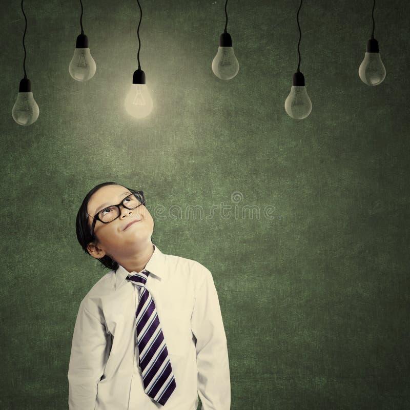 Piccolo imprenditore sveglio che esamina lampadina accesa immagini stock