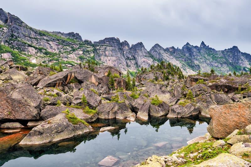 Piccolo lago della montagna in moraine glaciale dai grandi massi immagine stock libera da diritti