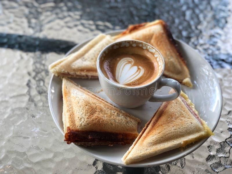Piccolo Latte art koffiekopje en boterham met warme ham kaas in witte plaat op de glazen tafel stock foto's