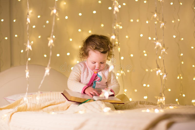 Piccolo libro di lettura sveglio della ragazza del bambino nella stanza scura con le luci di Natale immagini stock libere da diritti