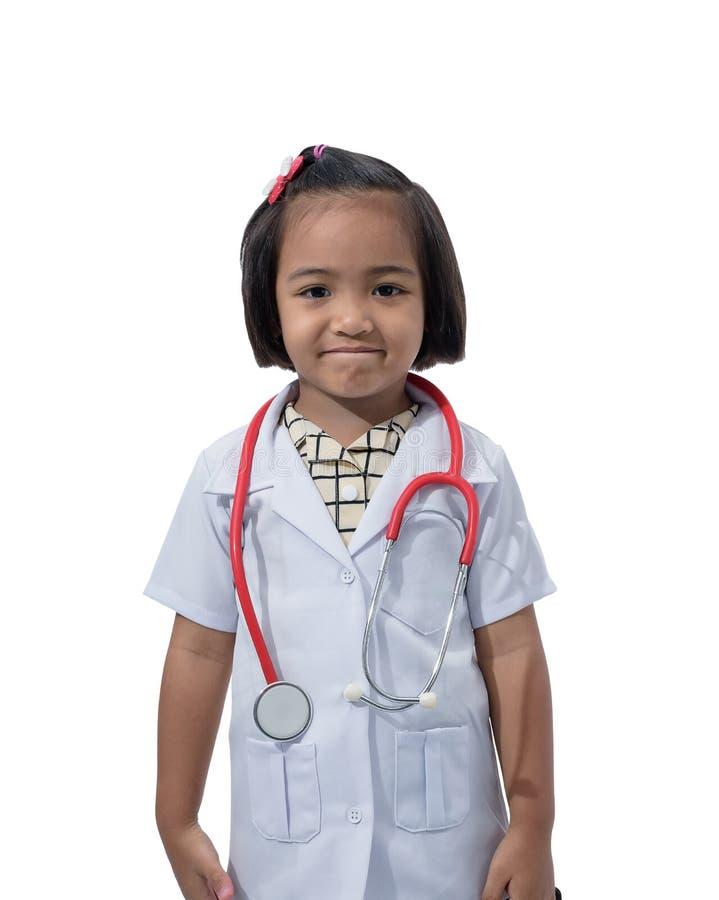 Piccolo medico asiatico sveglio della ragazza che sorride e che tiene stetoscopio mentre portando l'uniforme di medico fotografie stock