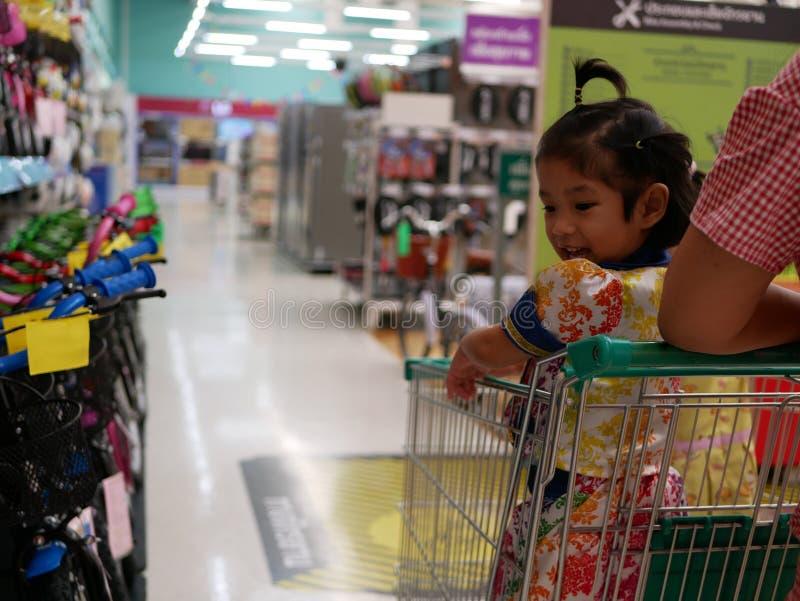 Piccolo neonata asiatica in un carrello, si eccita per vedere molte bici nei colori differenti in un supermercato fotografia stock libera da diritti