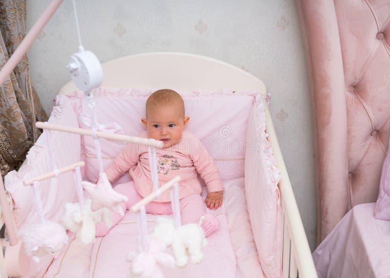 Piccolo neonata che si siede in sua greppia fotografie stock