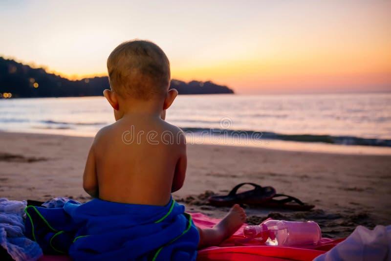 Piccolo neonata sotto 1 anno Sedendosi da solo sulla spiaggia sabbiosa e guardare il tramonto fotografia stock