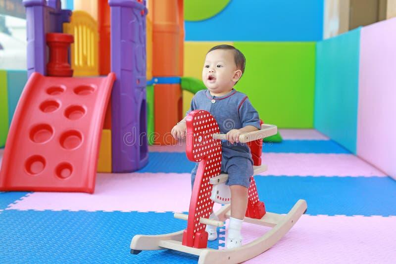 Piccolo neonato adorabile che gioca cavallo sul campo da giuoco, oscillazione di legno immagine stock