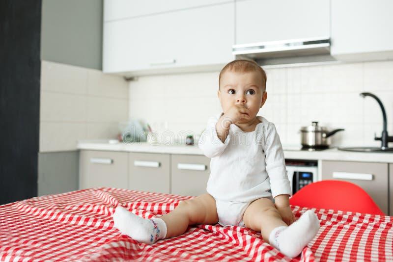 Piccolo neonato adorabile che si siede sulla tavola con la tovaglia rossa in cucina, tenente mano in bocca e guardante da parte c immagini stock