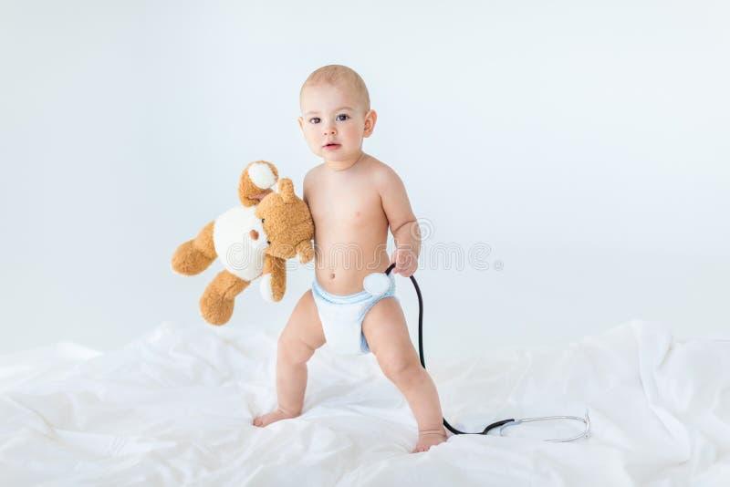 Piccolo neonato adorabile che sta sul letto e che tiene stetoscopio con l'orsacchiotto fotografia stock libera da diritti