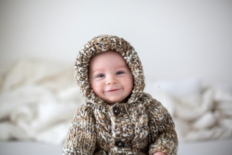 Piccolo neonato che gioca a casa a letto, vestito nel kni fatto a mano fotografie stock libere da diritti