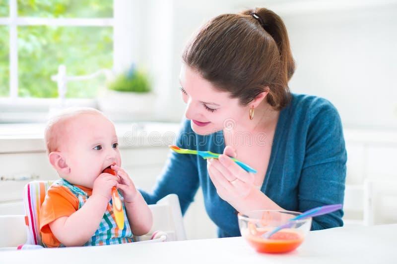 Piccolo neonato che mangia il suo primo alimento solido fotografia stock libera da diritti