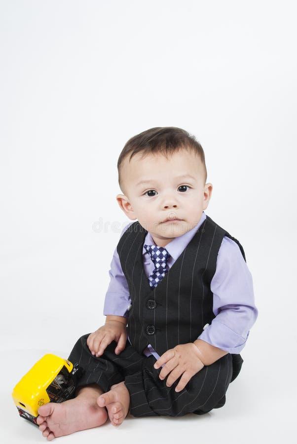 Piccolo neonato che si siede sul pavimento fotografie stock