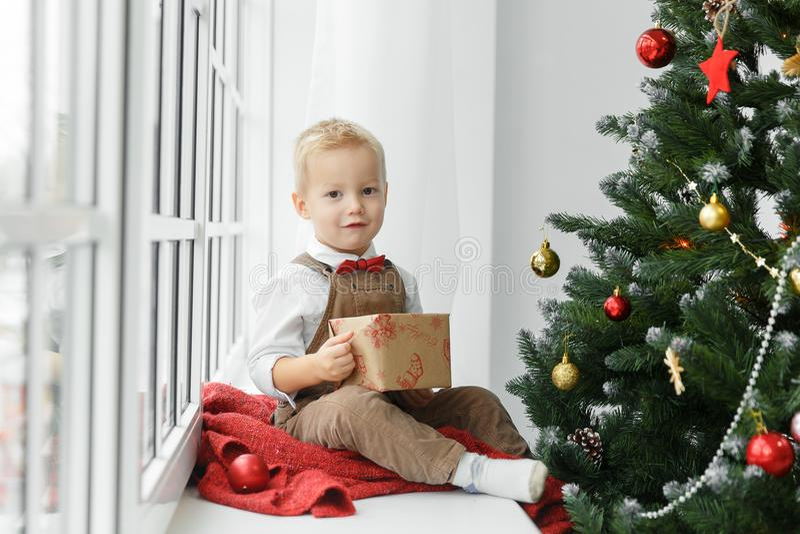 Piccolo neonato con il presente in sue mani che si siedono vicino all'albero di Natale e che esaminano macchina fotografica immagini stock libere da diritti