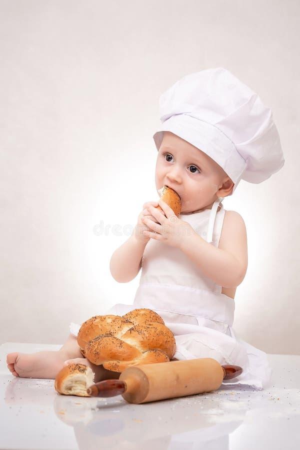Piccolo neonato del panettiere con la pagnotta condita in cappello del cuoco unico, ridente felicemente fotografia stock