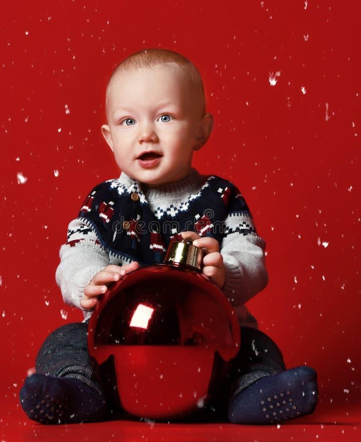 piccolo neonato felice con la palla a casa sopra neve immagini stock