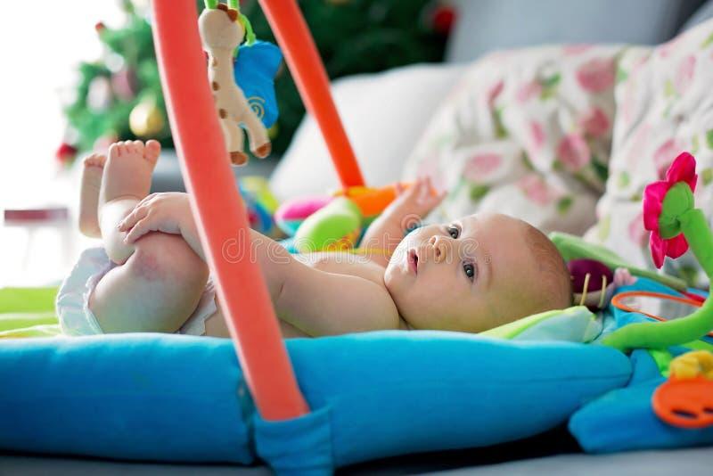 Piccolo neonato, giocante con i giocattoli variopinti a casa immagini stock