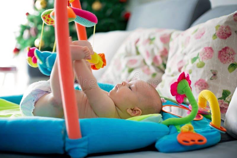 Piccolo neonato, giocante con i giocattoli variopinti a casa immagini stock libere da diritti