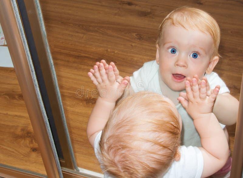 Piccolo neonato nella riflessione di specchio fotografia stock