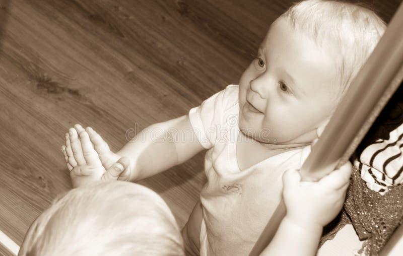 Piccolo neonato nella riflessione di specchio in bianco e nero fotografia stock