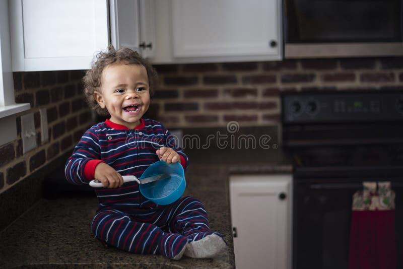 Piccolo neonato nero sveglio sorridente che gioca nella cucina fotografie stock libere da diritti