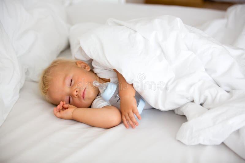 Piccolo neonato sveglio, addormentato con la bottiglia con il latte di formula immagine stock