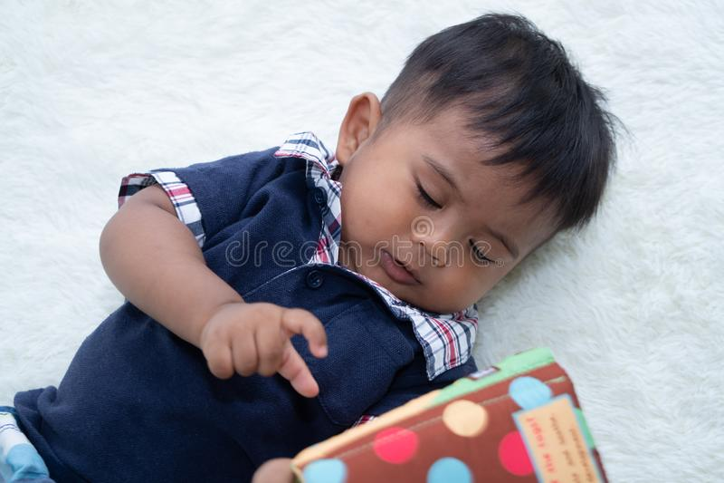 Piccolo neonato sveglio che legge il libro immagine stock