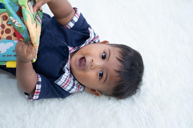 Piccolo neonato sveglio che legge il libro fotografia stock