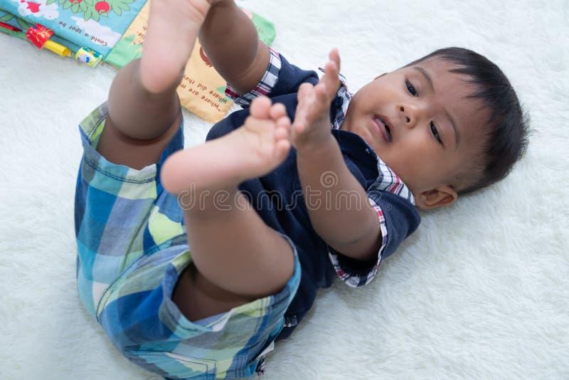Piccolo neonato sveglio che legge il libro fotografie stock
