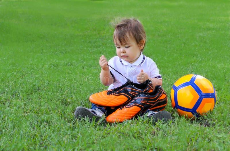 Piccolo neonato sveglio che si siede con il pallone da calcio di orage sugli stivali di calcio della tenuta dell'erba verde in su fotografia stock libera da diritti