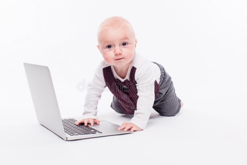Piccolo neonato sveglio che si siede su un fondo bianco davanti alla a fotografia stock libera da diritti