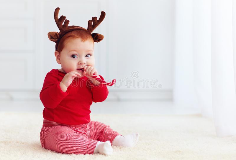 Piccolo neonato sveglio con gli ossequi dolci di natale dell'assaggio della banda della renna, seduta della testarossa sul pavime fotografie stock