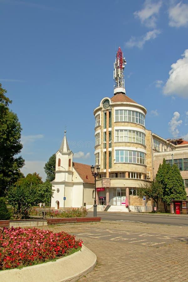 Piccolo nido evangelico modesto della chiesa ad una costruzione di appartamento moderna cilindrica in Alba Iulia, Romania fotografia stock libera da diritti