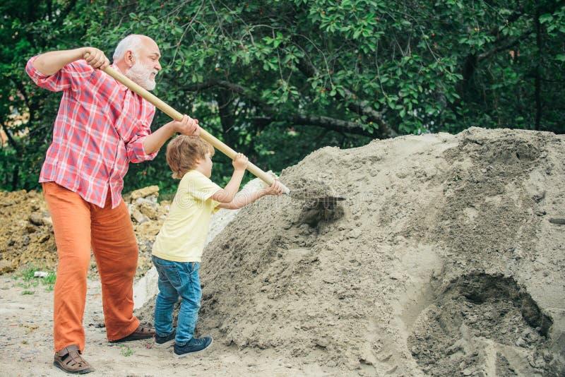 Piccolo nipote che aiuta suo nonno con il lavoro della costruzione Concetto di infanzia Nipote futuro del lavoratore con il nonno immagine stock libera da diritti