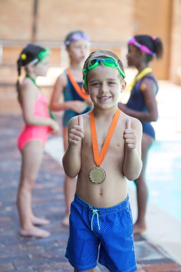 Piccolo nuotatore che mostra i pollici su al poolside fotografia stock libera da diritti