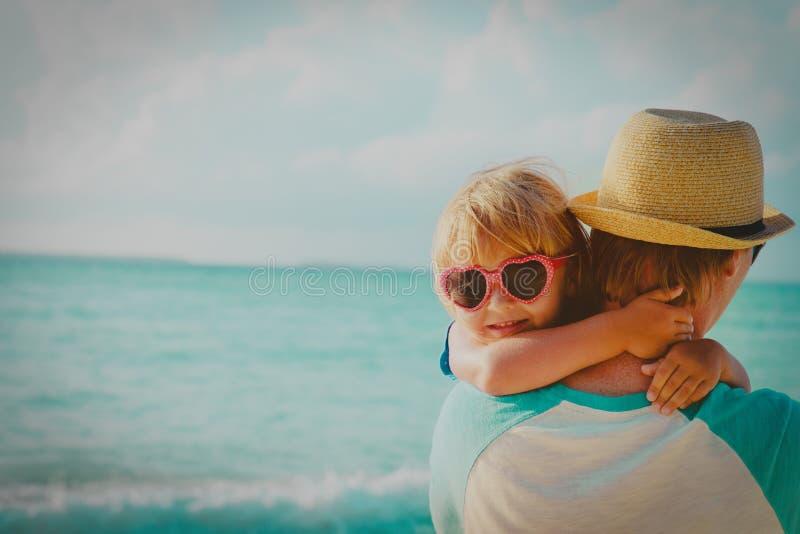 Piccolo papà sveglio felice dell'abbraccio della figlia alla spiaggia fotografia stock