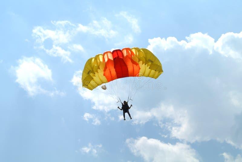 Piccolo paracadutista con il paracadute rosso arancio del yelow colourful su concorrenza paracadutante fotografia stock