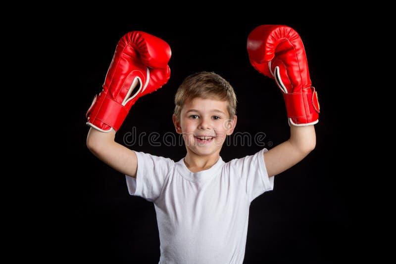 Piccolo pugile estremamente felice e riuscito con entrambe le mani su in guantoni da pugile rossi fotografia stock
