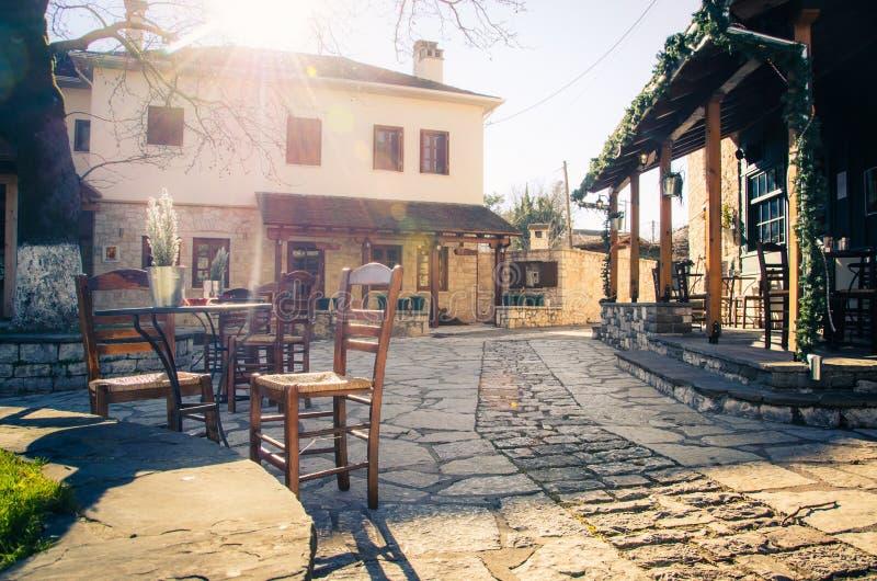 Piccolo quadrato pavimentato tradizionale con il caffè e le vie strette autentiche in Nissaki, Giannina immagine stock