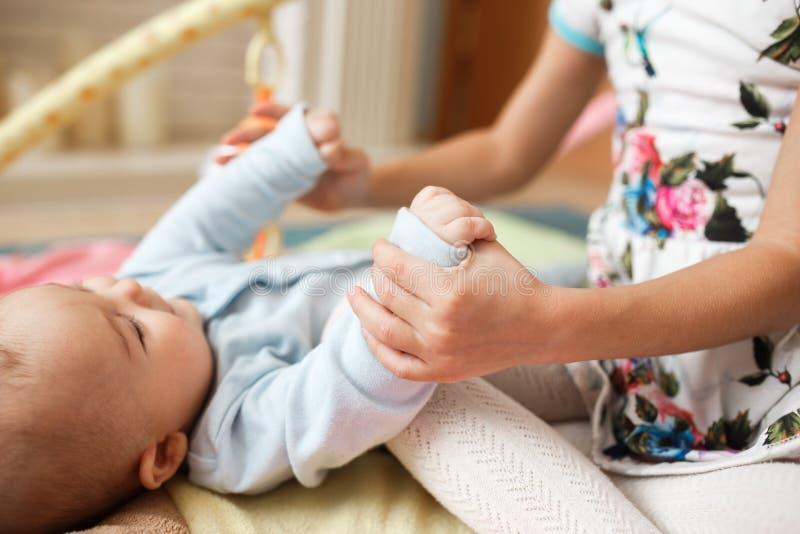 Piccolo ragazza affascinante si tiene per mano suo fratello minuscolo che si trova sul tappeto sul pavimento nella stanza fotografia stock libera da diritti