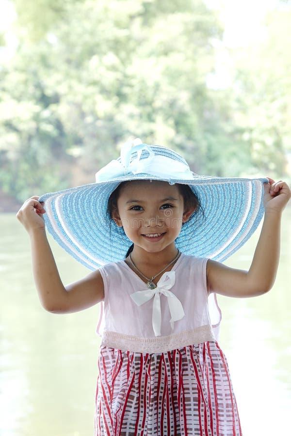 Piccolo ragazza asiatica all'aperto in cappello di estate immagini stock libere da diritti