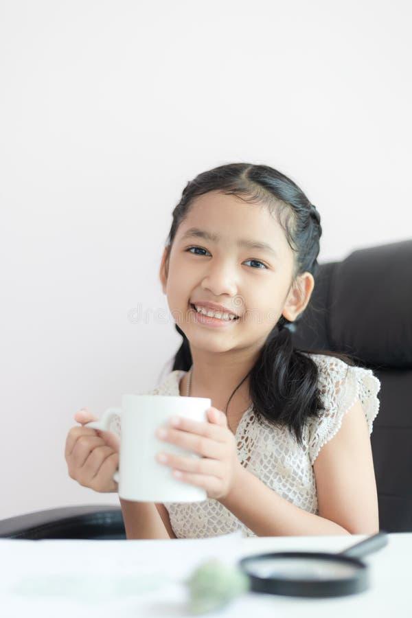 Piccolo ragazza asiatica che tiene tazza bianca e sorriso con profondità di campo bassa del fuoco scelto di felicità fotografia stock
